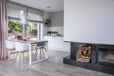 Modern fireplace and wood in a spacious dining room interior with white chairs by a wooden table and big windows