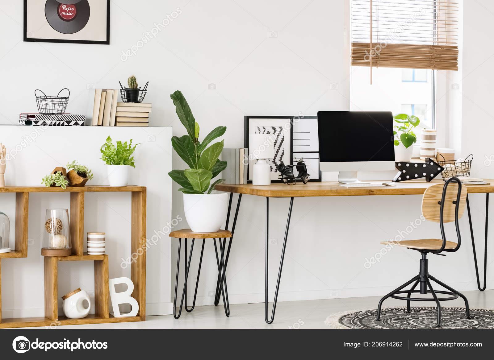 Pianta sgabello accanto alla scrivania legno con computer desktop