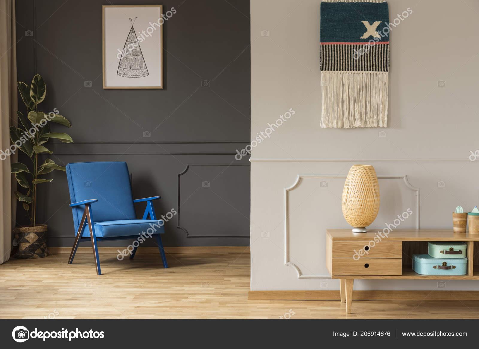 Blauwe leunstoel tegen grijs muur met poster houten kast woonkamer