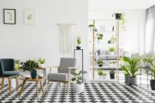 Photo Wooden table between armchairs on checkered floor in living room interior with plants and posters. Real photo