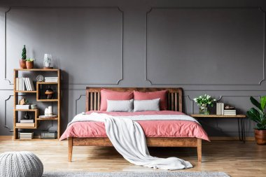 Grey blanket on pink wooden bed in bedroom interior with books, plants and pouf