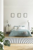 Real photo of bright bedroom interior with three simple posters, striped carpet and pastel green sheets on double bed
