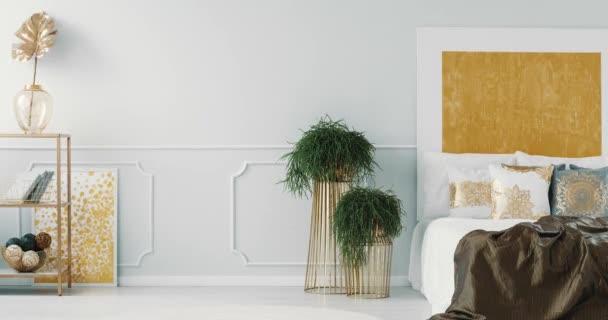 Cuscini bianchi e grigi con reticolo delloro sul letto allinterno di elegante camera da letto con oro dipinto. Video con modifica fotogrammi
