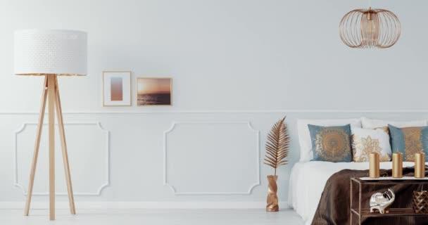 Zlatá lampa nad postel s bílou a šedou polštáře v interiéru světlý pokoj s zlaté křeslo. Video