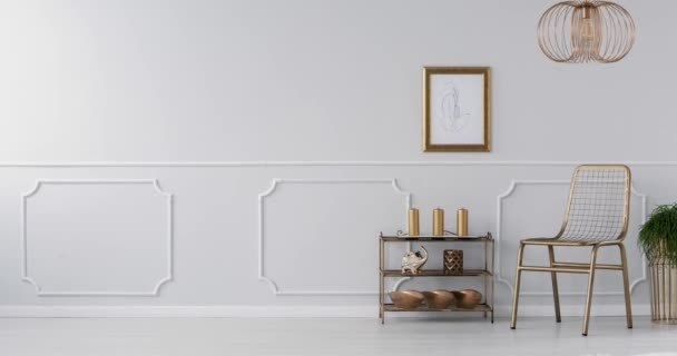 Video of a gold, elegant living room interior with a drawing on gray wall with molding, gold armchair and plants
