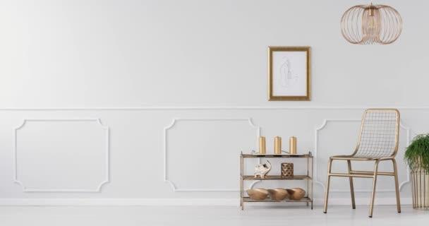 Video z zlaté židle, regál s dekoracemi, rostliny na zlaté stánky a šedivá zeď s hnětení v interiéru obývací pokoj
