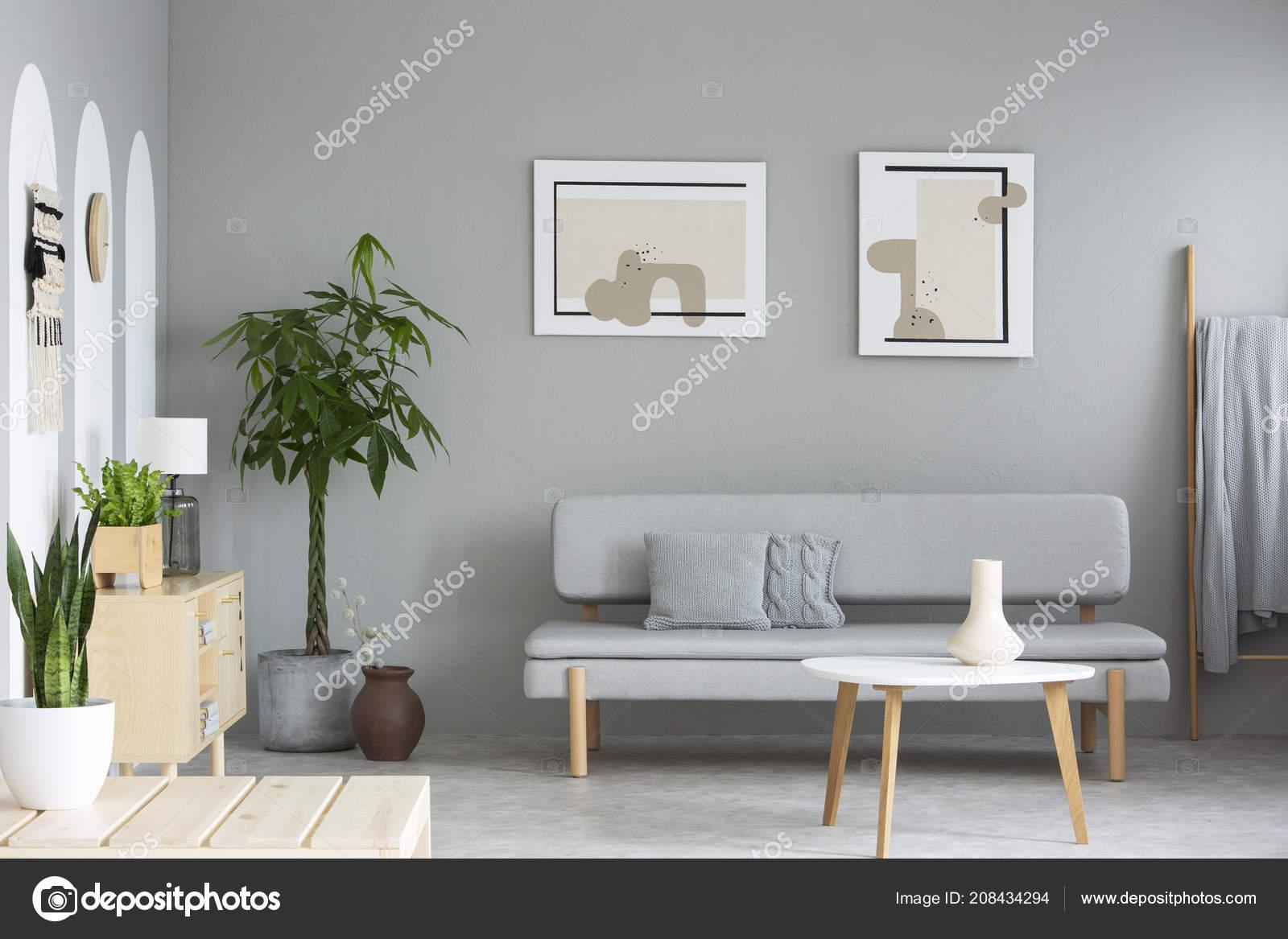 Houten tafel grijs sofa eenvoudige woonkamer interieur met posters