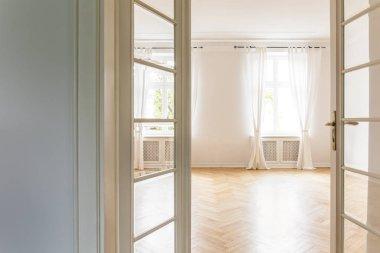 View through open glass door on an empty, bright bedroom interior with big windows, white walls and herringbone floor