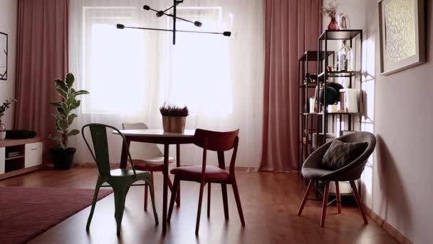 Závěs v interiéru útulná jídelna se stolem, židlemi, rostliny a police. Video