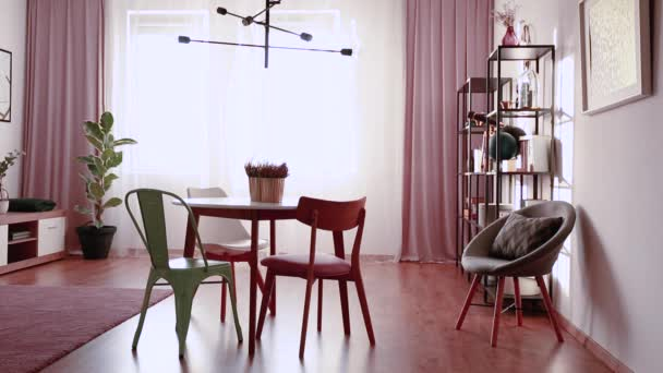 Video of a curtain moving in a pink dining room interior with a table, chairs, lamp, window and armchair
