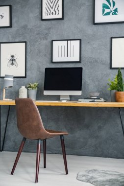 Simple desk with a computer and plant, paintings on the wall and brown chair in a home office interior. Place your graphic here