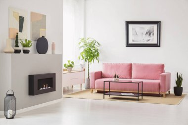 Posters on walls in Scandi sitting room interior with pink velvet couch, fresh plants, fireplace and decor