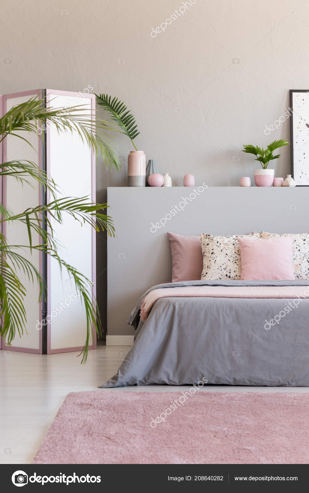 Pink carpet in front of grey bed with cushions in bedroom interior with screen and plants real photo photo by photographee eu