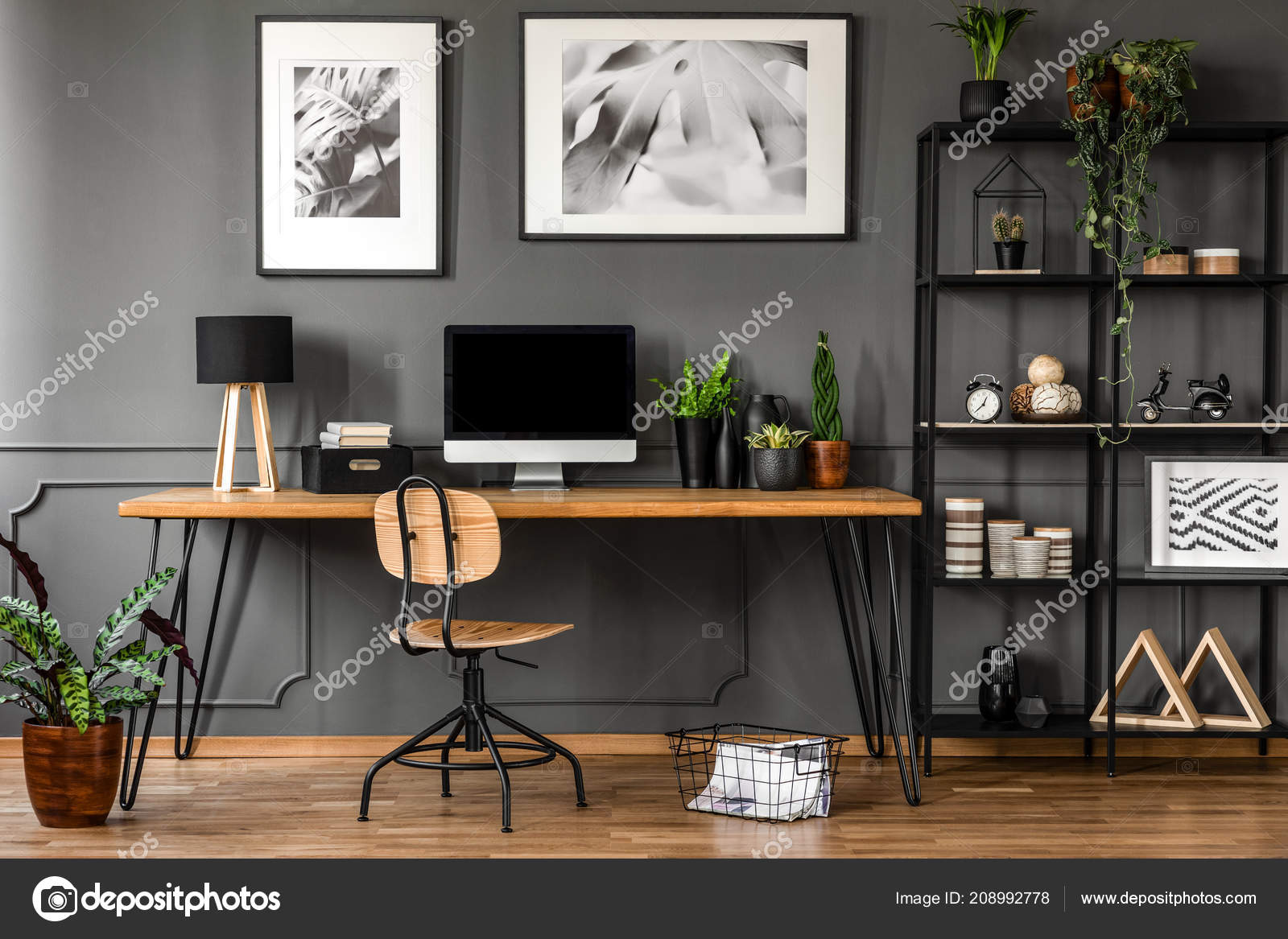 Posters on grey wall above wooden desk in natural home office interior with  plants and lamp 35