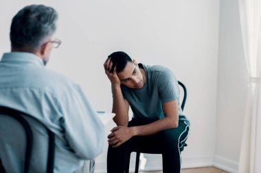 Depressed teenager looking away while talking to his therapist