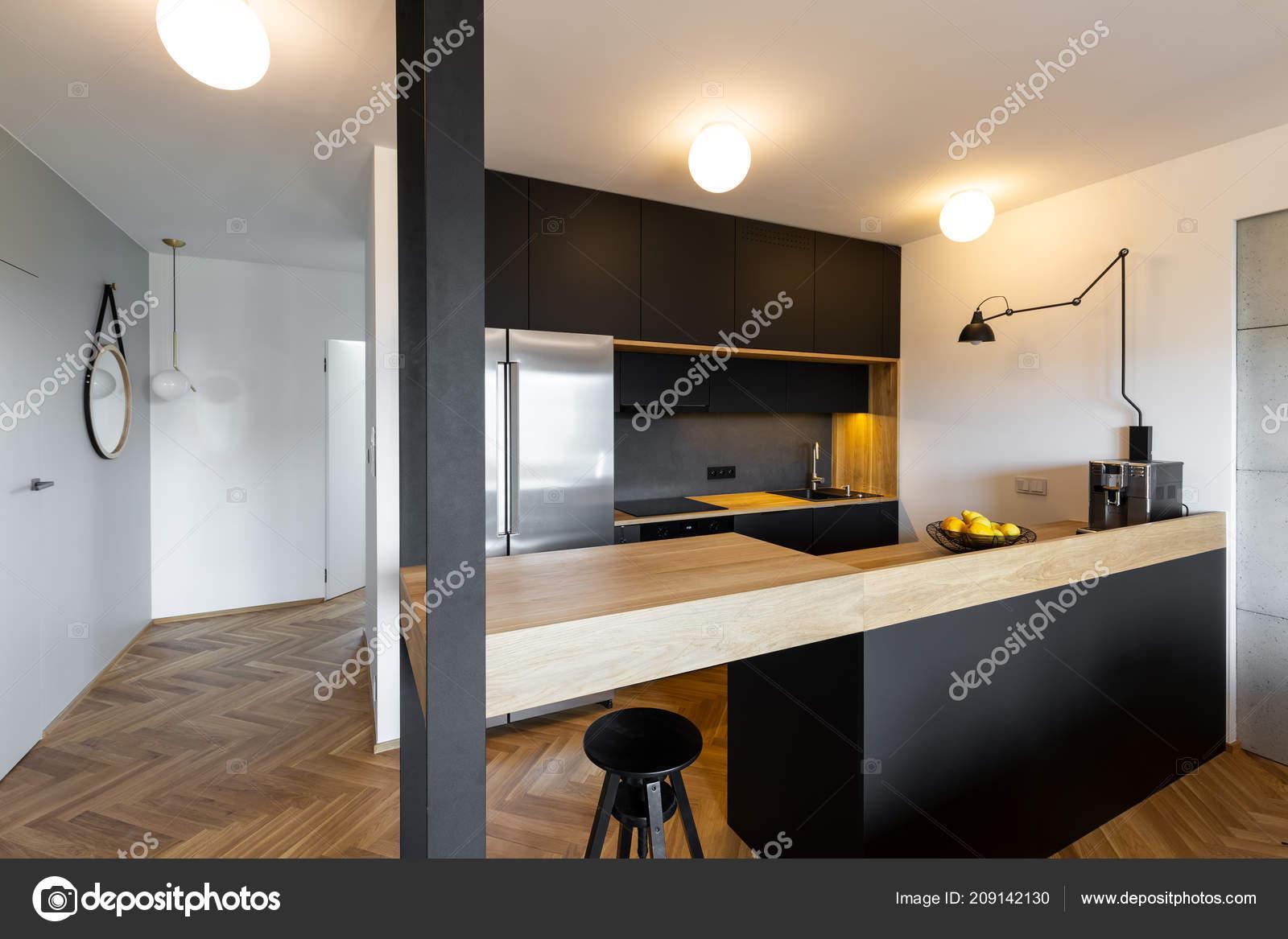 Sgabello sotto beige appoggio interno cucina nera con luci lampada
