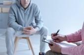 Ustaraný mladý muž sedí na židli v rozostřeného pozadí. V přední rukou psaní poznámek během schůzky individuální terapie specialista. Kopírovat prostor.