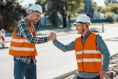 Smiling workers in reflective vests and white helmets greeting each other stock vector