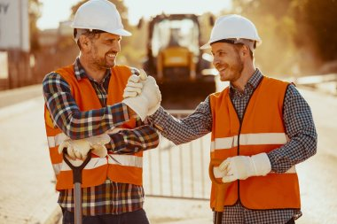Smiling coworkers in reflective vests and white helmets after roadwork stock vector