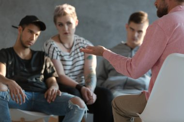 A professional counselor talking about overcoming anger and anxiety to rebel teenagers during a group psychotherapy session.