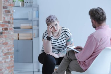 Rebellious young girl with lack of self-acceptance and drug addiction problem during an individual psychotherapy session with an intervention specialist.