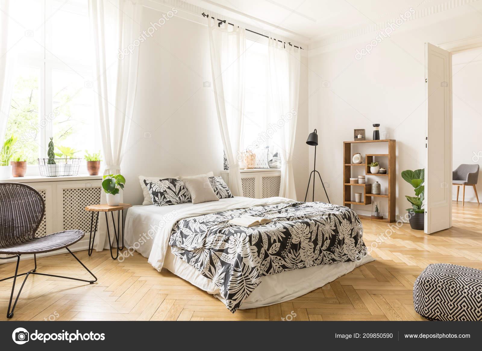 Interno una camera letto con parquet spina pesce pareti bianche