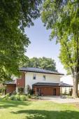 Fotografie Stromy v zahradě moderního domu. Reálné Foto