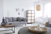 Echtes Foto von einem natürlichen Tablett mit Glasvasen und eine Kerze am Tisch mit gefleckten Tischdecke im Vordergrund ein Scandi Wohnzimmer Interieur mit grauen sofa