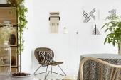 Gemusterte Kissen auf Stuhl und Pflanze in weißen Boho Wohnzimmer Interieur mit Plakaten auf Tisch. Echtes Foto