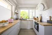 Okna v interiéru bílá kuchyňská linka s šedé skříňky a dřevěná deska. Reálné Foto