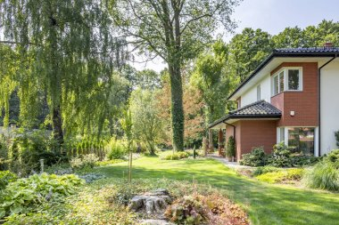 Beautiful garden with trees and shrubs next to a big house. Real photo