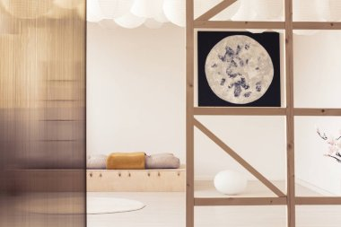 Poster and screen in white minimal bedroom interior with pillows on wooden bed. Real photo