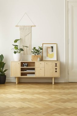 Vintage cabinet with plants, poster and wall decoration above in simple living room interior with wooden parquet. Real photo