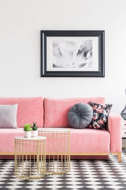 Poster above pink sofa with pillows in white living room interior with gold tables. Real photo