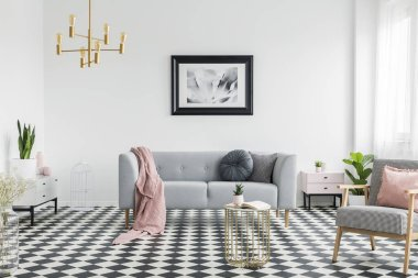 Pink blanket and pillows on grey couch in white living room interior with poster and armchair. Real photo