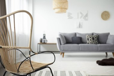 Close-up on armchair in living room interior with grey couch with pillows and lamp. Real photo with blurred background