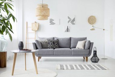Real photo of a simple living room interior with cushions on gray sofa, paintings on white wall and cherries on a coffee table