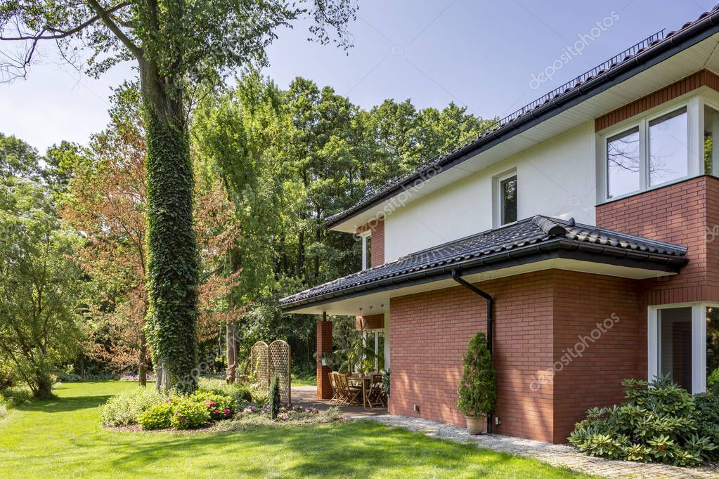 Red brick wall of house with roof and windows next to trees and garden