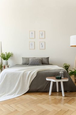 White blanket on grey bed in bright bedroom interior with posters and wooden table. Real photo