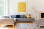 Fotografie Gelbe Bemalung und Lampe im modernen Wohnzimmerinterieur mit grauem Ecksofa. echtes Foto