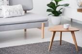 Pohár na dřevěný konferenční stolek a rozmazané pozadí grafické polštáři na šedá pohovka v obýváku bílý interiér