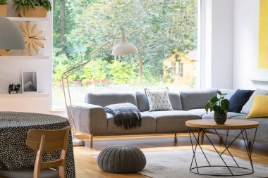 Pouf next to table in modern living room interior with grey corner sofa and window. Real photo