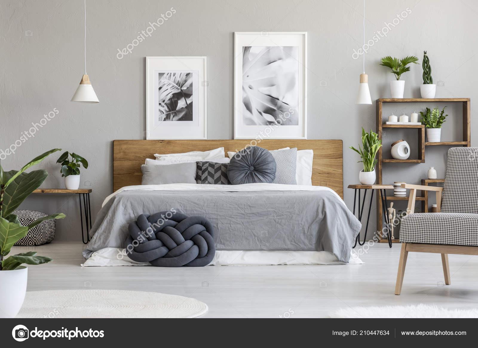 Posters boven houten bed grijs slaapkamer interieur met planten