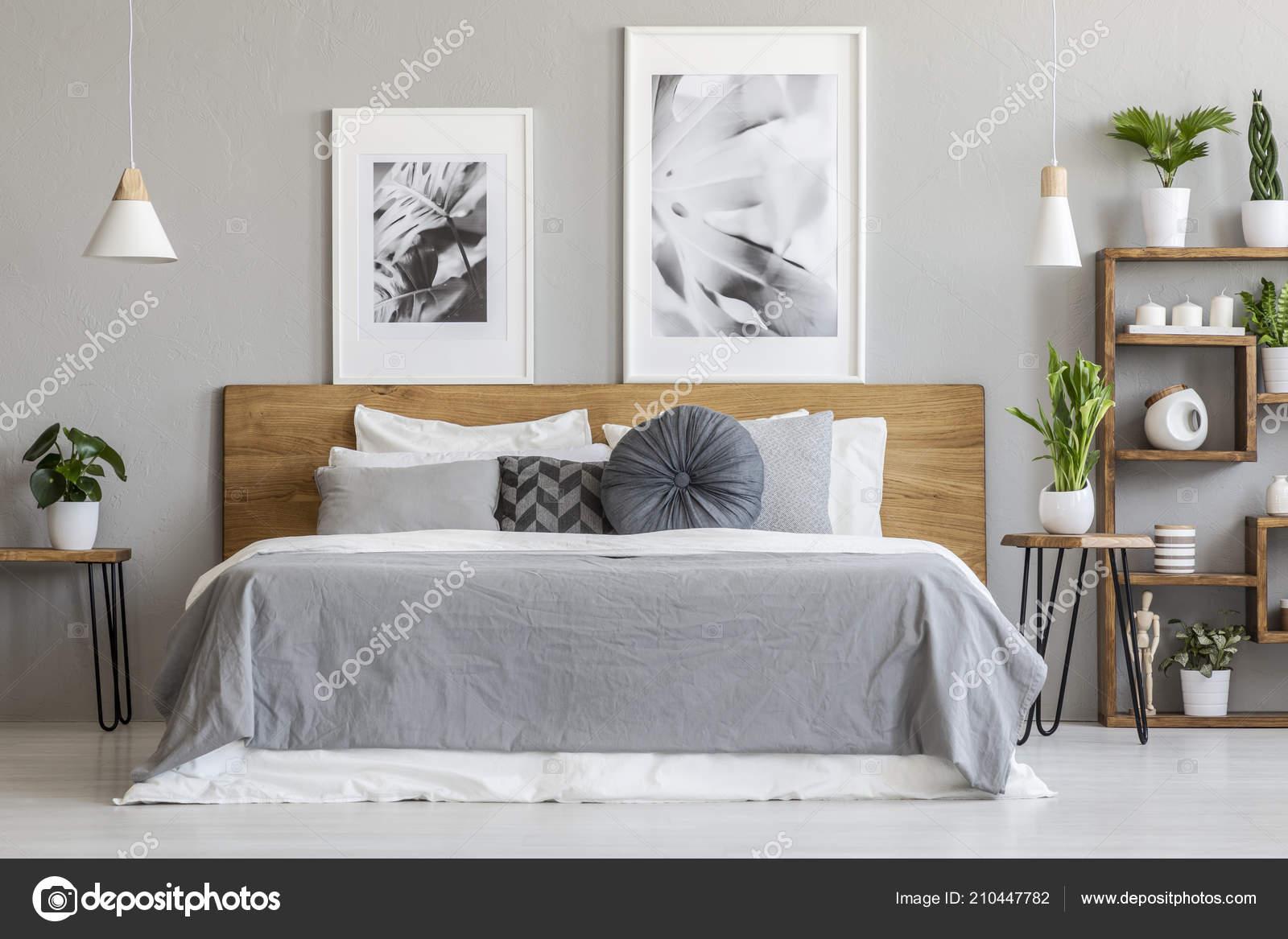 Slaapkamer Interieur Grijs : Grijze lakens kussens houten bed slaapkamer interieur met posters