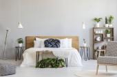 Polštář modrý uzel na bílé dřevěné posteli v interiéru šedou ložnice s křeslem a rostliny. Reálné Foto