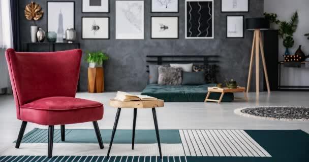 Video sekvence z různých křesel, stojící na modré a bílé koberce, u stolice s otevřenou knihou, v popředí interiér rozmazané ložnice