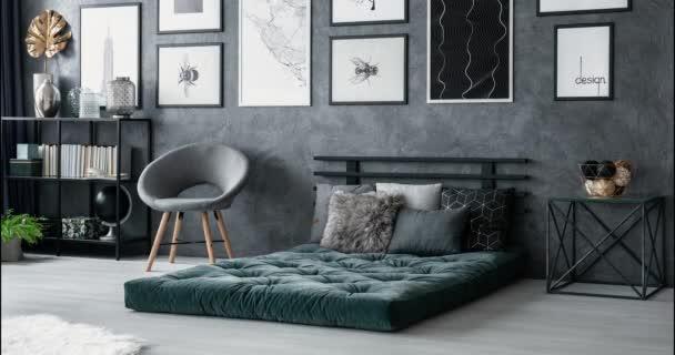 Sekvence stop-motion design interiéru ložnice. Video z polštářů na zelené matrace a kovový stolek šedé, betonové zdi.