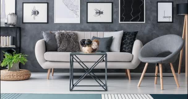 Video z křesla šedé, černé, modré a červené měnící se vedle béžovou pohovku s dekorativní polštáře v interiéru obývacího pokoje šedé a bílé. Stop-motion sekvence