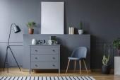 Šedá skříň mezi černou lampou a židle v interiéru obývacího pokoje s maketa plakát. Reálné Foto