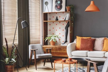 Grey armchair next to lamp in orange vintage living room interior with sofa next to cabinet